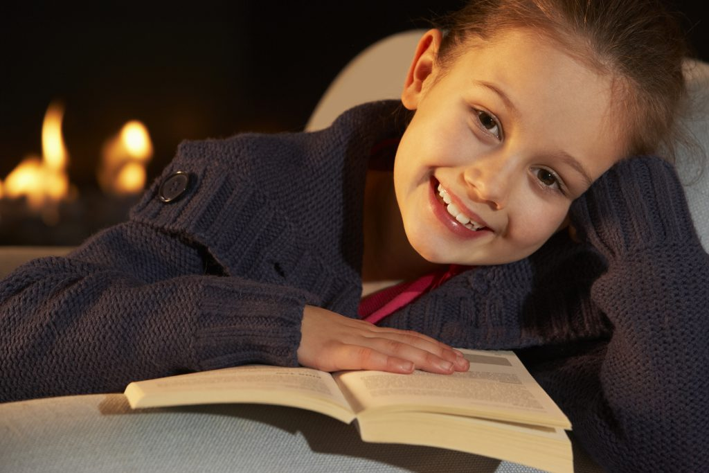 Portrait 7 year old girl reading by firelight